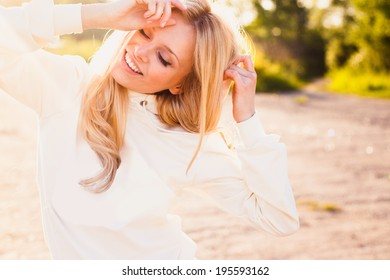 Cheerful smiling girl standing outdoors in a sunny summer day