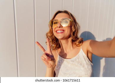 Cheerful smiling girl in yellow sunglasses showing a two fingers, peace sign, while taking a selfie. Outdoors