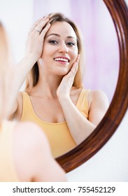 Cheerful smiling glad woman having a look at her face at the mirror on the wall