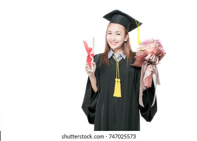 Cheerful smiling graduating woman with diploma and bouqet of beautful flowers in an academic gown.Graduate woman student wearing graduation hat and gown on white background.Pride beautiful asian girl.