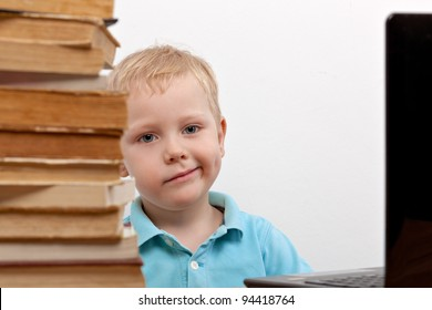 Cheerful smiling  little boy sitting at the table. Looking at camera. School concept