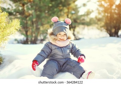 Cheerful smiling little child playing on snow in winter day