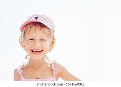A cheerful, smiling little girl in a rose-colored hat narrowed her eyes with pleasure on a vacation by the sea.