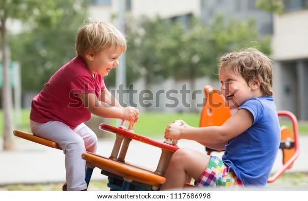 Lächelnde kleine Mädchen, die sich auf dem Spielplatz amüsieren
