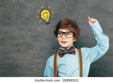 Cheerful smiling little kid (boy) against  chalkboard; raised his hand up. Looking at camera. School concept