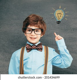 Cheerful smiling little kid (boy) against chalkboard. Looking at camera. School concept