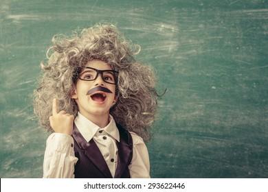 Cheerful smiling little kid (boy) against chalkboard. Looking at camera. Little Einstein style. School concept