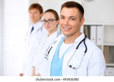 Cheerful smiling male doctor with medical staff at the hospital