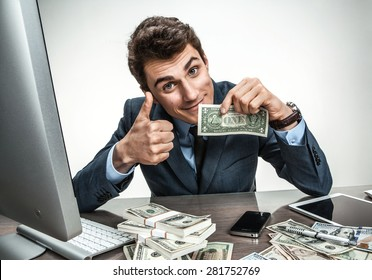 Cheerful smiling man showing thumbs up success sign / modern businessman at his desk with computer and a lot of money