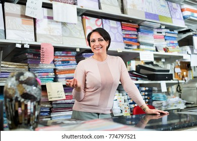 Cheerful smiling  mature saleswoman offers  goods  in  textile shop