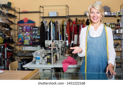 cheerful smiling mature woman standing in sewing studio ready to take order