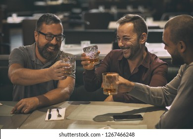 Cheerful smiling men holding glasses with alcohol beverages and laughing. Three friends spending time together and having fun in bar. Men drinking scotch, whiskey or brandy.