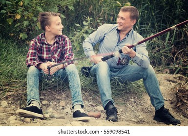 cheerful smiling middle-aged father and teenager son fishing together on lake shore