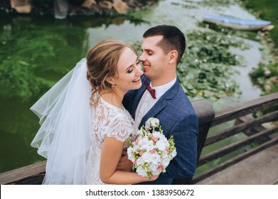 Cheerful and smiling newlyweds are hugging on a wooden bridge, against the background of the river and greenery. Stylish groom in a suit and a beautiful curly bride in nature. Closeup portrait.