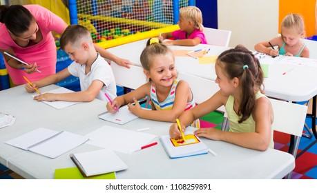 cheerful smiling primary school children sitting at school desks at lesson