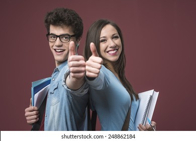 Cheerful smiling students thumbs up and holding textbooks