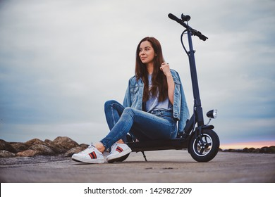 Cheerful smiling woman is chilling on her new electro scooter at seaside in cloudy day.