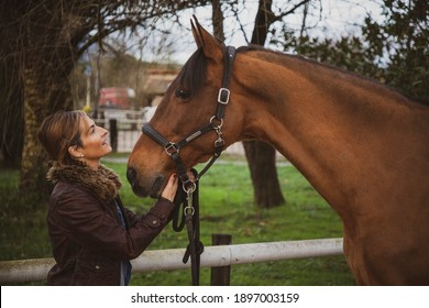 Cheerful and smiling woman dressed in a brown jacket looking at her horse at the ranch