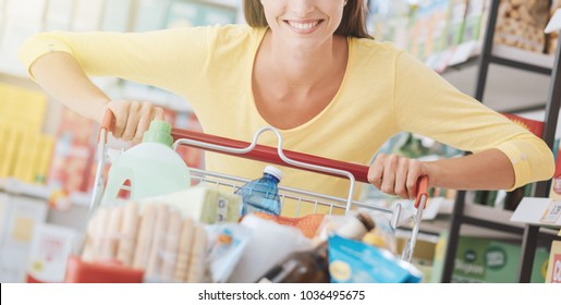 Cheerful smiling woman enjoying grocery shopping, she is pushing a cart along the store aisles