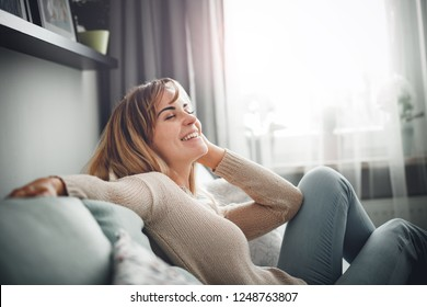 Cheerful smiling woman full of positive emotions sitting on sofa at home