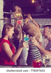 Cheerful smiling woman and man joying in the night club with drinks in the hand