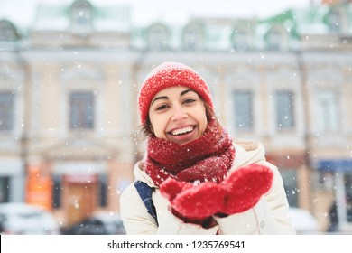 Cheerful smiling woman in white down jacket and red cap, scarf and mittens walking on the snowy street and catching snowflakes after blizzard in city.