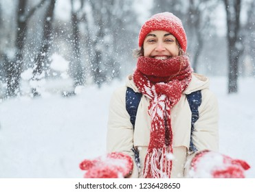 Cheerful smiling woman in white down jacket and red cap, scarf and mittens walking and plaing snow and snowballs on the snowy street after blizzard in city. winter city after blizzards and snowfall.
