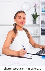 cheerful smiling woman writing down information from computer at office
