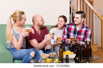 Cheerful smiling young adults drinking beer at home. Focus on man
