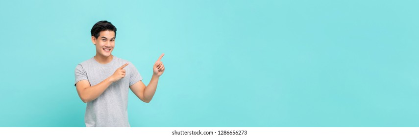 Cheerful smiling young Asian man pointing hands to copy space aside studio shot isolated on light blue banner bakground