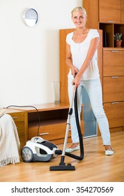 Cheerful smiling young blonde woman in jeans vacuuming floor at home