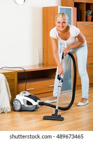 Cheerful smiling young blonde woman in jeans vacuuming floor and furniture