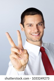 Cheerful smiling young businessman showing two fingers, or victory gesture, against grey background