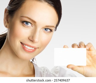 Cheerful smiling young businesswoman showing blank business or plastic credit card with copyspace area for slogan or text, on grey