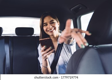 Cheerful smiling young female passenger in casual outfit sitting in car backseat with seatbelt fastened and using smartphone while giving direction to driver and pointing with finger