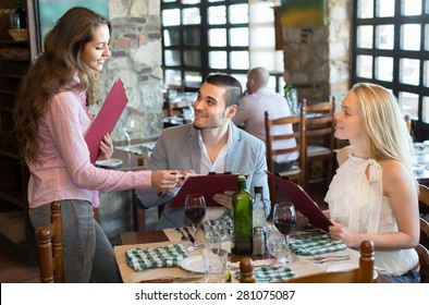 Cheerful smiling young female waiter serving restaurant guests. Selective focus