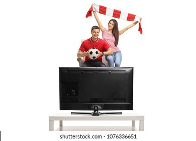 Cheerful soccer fans seated in an armchair watching a game of football on TV isolated on white background