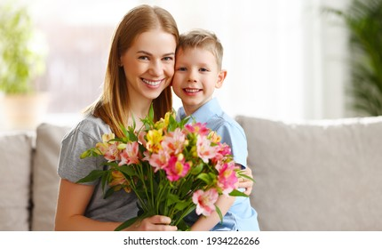 Cheerful son embracing mother sitting on sofa with bouquet of Alstroemeria flowers on Mothers Day