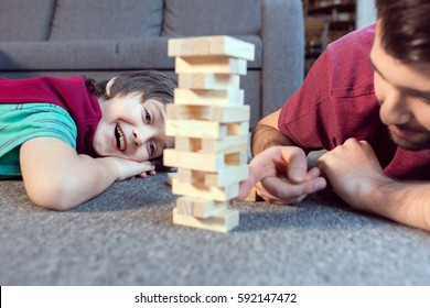 cheerful son and father playing jenga game at home
