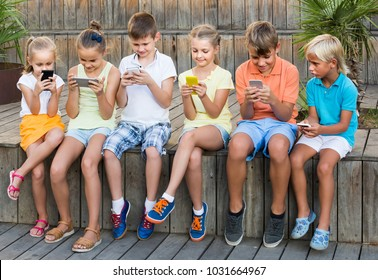 cheerful spanish  children in school age looking at mobile phones and sitting outdoors