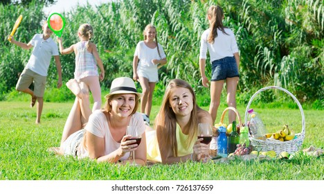 Cheerful spanish females on picnic outdoors on background with children playing active games