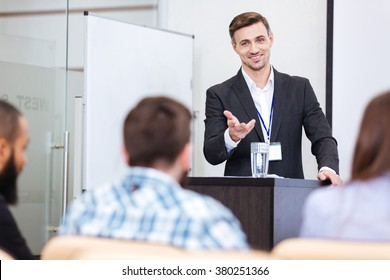 Cheerful speaker standing at the tribune in conference hall and pointing on male in audience