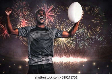Cheerful sportsman with clenched fist holding rugby ball against fireworks exploding over football stadium