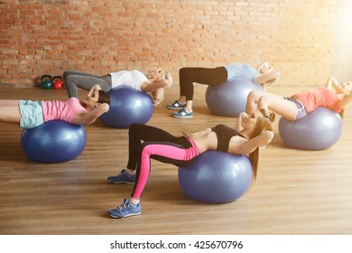 Cheerful sporty girls do sit ups