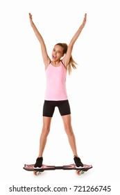 Cheerful sporty teen girl standing on waveboard with hands up,isolated on white background
