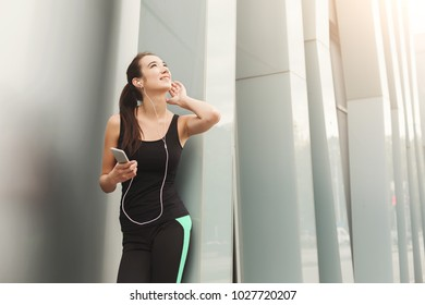 Cheerful sporty woman having rest after workout. Young fitness girl listening to music on smartphone, leaning on city construction, copy space