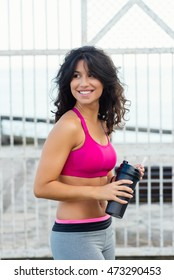 Cheerful sporty woman taking an urban fitness workout rest for drinking water.