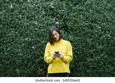 Cheerful sporty woman texting on smart phone in autumn at the park.