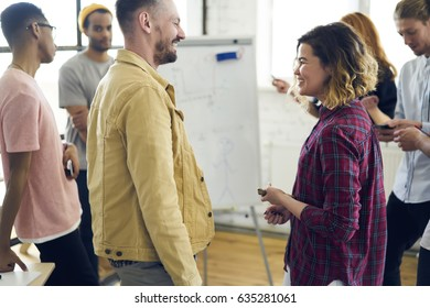 Cheerful staff members discussing creative ideas in positive atmosphere while collaborating with partners, hipsters in good mood having fun and joking with each other during work break indoors