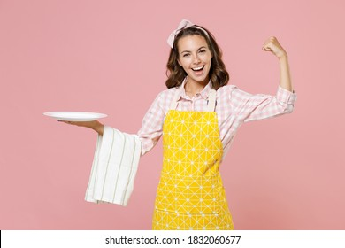 Cheerful strong young woman housewife in yellow apron hold empty plate dishcloth towel showing biceps muscles doing housework isolated on pastel pink background studio portrait. Housekeeping concept
